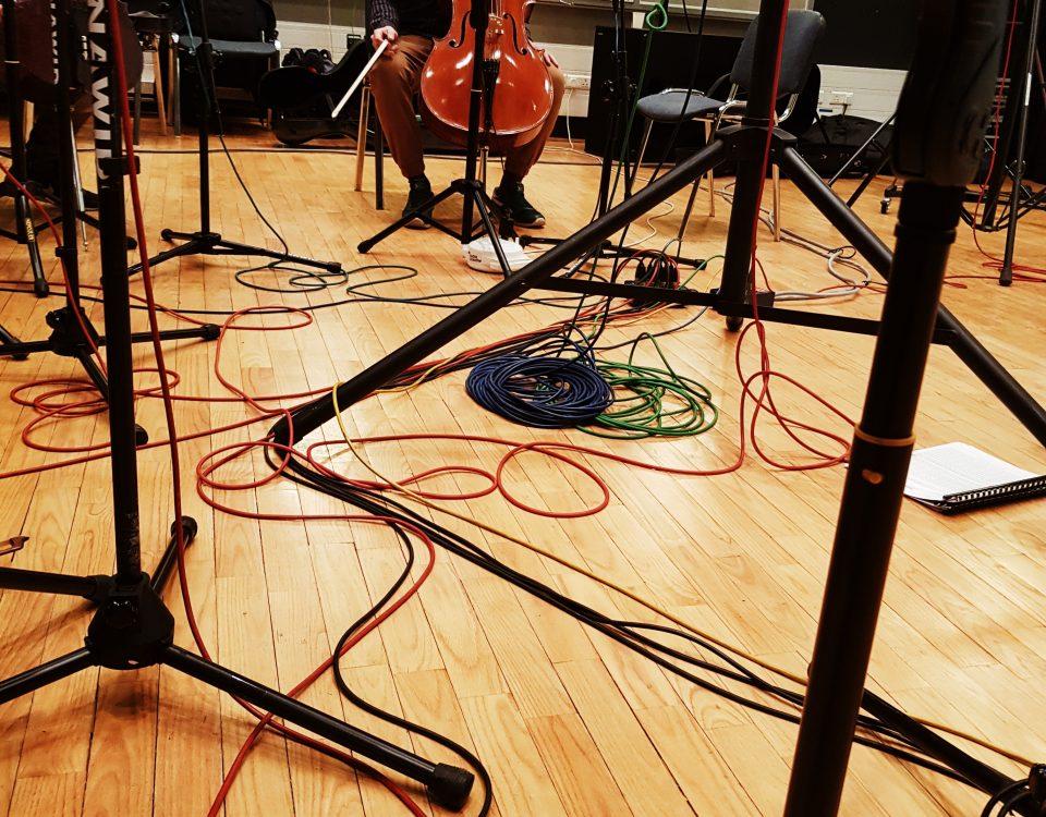 wiolonczela, kable i pulpity - drewniane instrumenty na drewnianej podłodze - przygotowania do nagrania krążka CD w Radiu Kraków